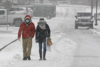 A couple walks through heavy snow, Saturday, Dec. 5, 2020, in downtown Marlborough, Mass. The northeastern United States is seeing the first big snowstorm of the season. (AP Photo/Bill Sikes)