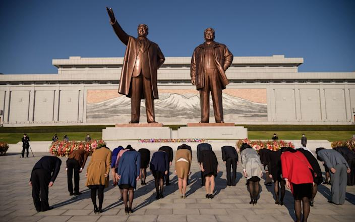 People bow before the statues of late North Korean leaders Kim Il Sung and Kim Jong Il at Mansu hill as the country marks the 75th founding anniversary of the Workers' Party of Korea - AFP
