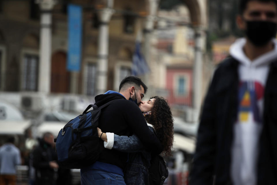 A couple kiss each other in Athens, Friday, Nov. 6, 2020. With a surge in coronavirus cases straining health systems in many European countries, Greece announced a nationwide lockdown. The lockdown takes effect at daybreak on Saturday across the country and will last until the end of the month. (AP Photo/Thanassis Stavrakis)
