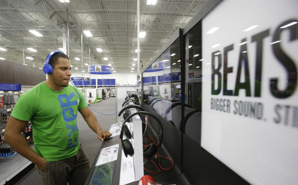 Eric Soriano listens to music with a pair of Beats headphones at a Best Buy store, Thursday, May 29, 2014, in Orlando, Fla. On Wednesday, May 28, 2014, Apple announced it acquired Beats Electronics, founded by rapper Dr. Dre and Jimmy Iovine. (AP Photo/John Raoux)