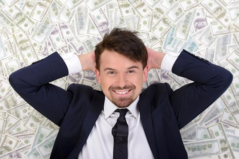 A wealthy businessman in a suit lying on a bed of cash.