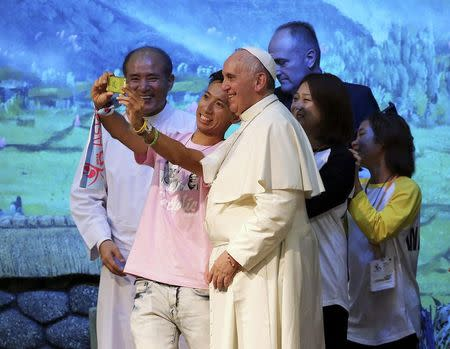 "Pope Francis (C) poses for a ""selfie"" with young people during a meeting with Asian youths at the Solmoe Shrine in Dangjin August 15, 2014. REUTERS/Ahn Young-joon/Pool"