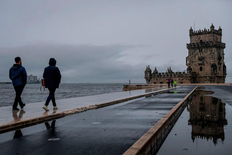 People walk along the Tagus River in Belem, Portugal, during storm Barbara on 20 October, 2020.  (AFP via Getty Images)