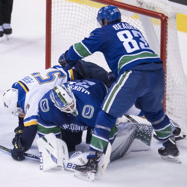 Vancouver Canucks center Jay Beagle (83) watches as St. Louis Blues left wing David Perron (57) falls over Canucks goaltender Jacob Markstrom (25) during the third period of an NHL hockey game Thursday, Dec. 20, 2018, in Vancouver, British Columbia. (Jonathan Hayward/The Canadian Press via AP)