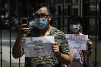 Protesters holds a slogan during a rally outside the Department of Justice in Manila, Philippines, Thursday Sept. 3, 2020. A Philippine court has ordered the early release for good conduct of U.S. Marine Lance Cpl. Joseph Scott Pemberton convicted in the 2014 killing of transgender Filipino Jennifer Laude which sparked anger in the former American colony. (AP Photo/Aaron Favila)
