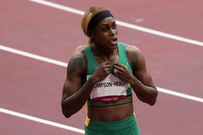 Elaine Thompson-Herah, of Jamaica, wins a heat in the women's 100-meter run at the 2020 Summer Olympics, Friday, July 30, 2021, in Tokyo. (AP Photo/Charlie Riedel)