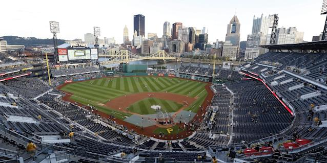The Pittsburgh skyline stands beyond the outfield wall as the Cincinnati Reds take batting practice before their NL wild-card playoff baseball game against the Pittsburgh Pirates on Tuesday, Oct. 1, 2013, in Pittsburgh. (AP Photo/Keith Srakocic)