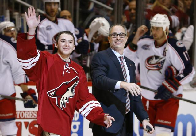 New Arizona Coyotes majority owner Andrew Barroway, right, walks onto the ice with son Jake Barroway, left, as they wave to fans before the ceremonial first puck drop prior to an NHL hockey game against the Columbus Blue Jackets Saturday, Jan. 3, 2015, in Glendale, Ariz. (AP Photo/Ross D. Franklin)