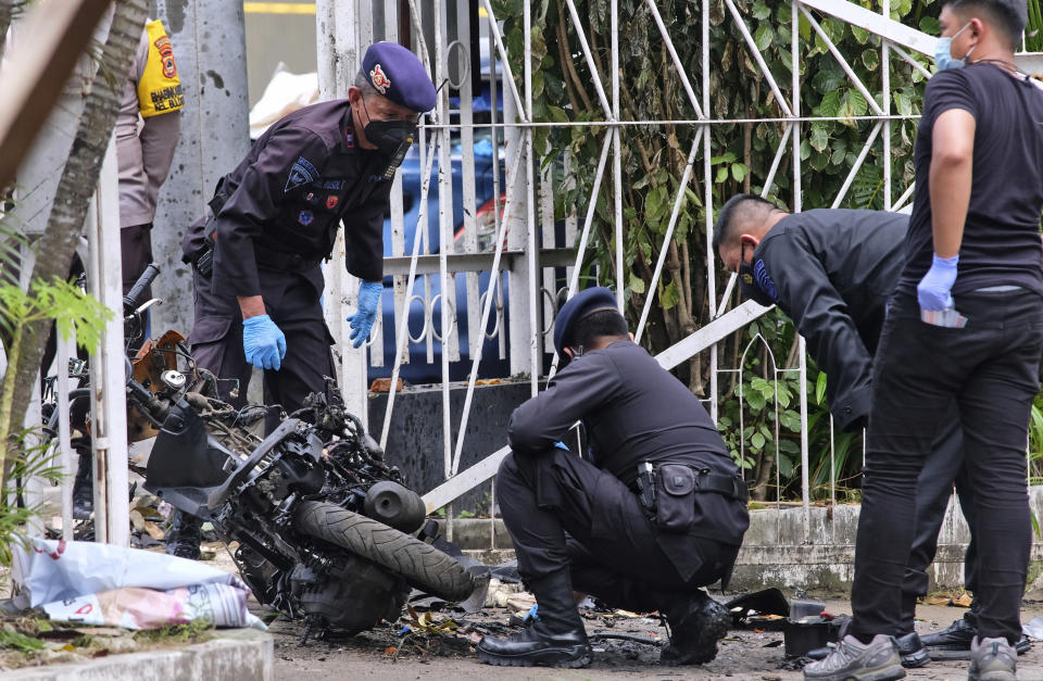 Members of a police bomb squad inspect the wreckage of a motorbike used to carry out Sunday's suicide bomb attack at the Sacred Heart of Jesus Cathedral in Makassar, South Sulawesi, Indonesia, Monday, March 29, 2021. Two attackers believed to be members of a militant network that pledged allegiance to the Islamic State group blew themselves up outside the packed Roman Catholic cathedral during a Palm Sunday Mass on Indonesia's Sulawesi island, wounding a number of people, police said. (AP Photo/Masyudi S. Firmansyah)