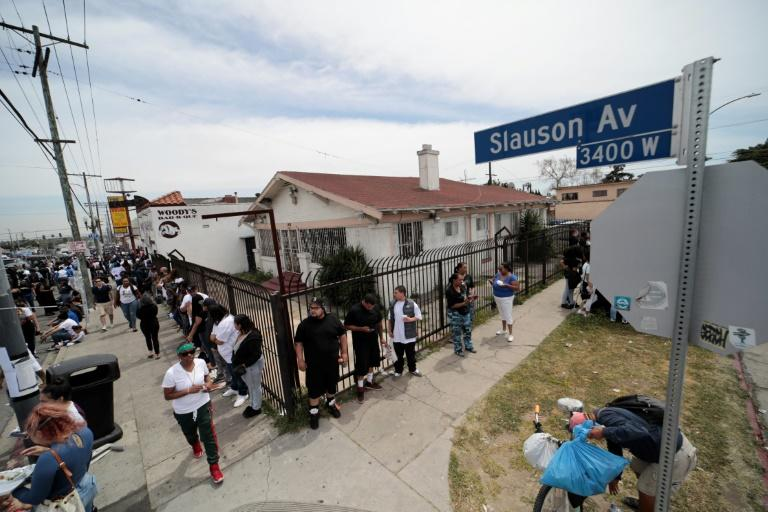 Fans and community members gather along the procession route for Nipsey Hussle following his memorial ceremony at the Staples Center in Los Angeles