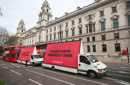 Vans with slogans aimed at Britain's Labour Party are driven around Parliament Square ahead of a debate on antisemitism in Parliament, in London, April 17, 2018. REUTERS/Hannah McKay