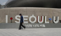 A man wearing a face mask walks in front of the display of South Korea's capital Seoul logo in Seoul, South Korea, Sunday, June 28, 2020. (AP Photo/Lee Jin-man)