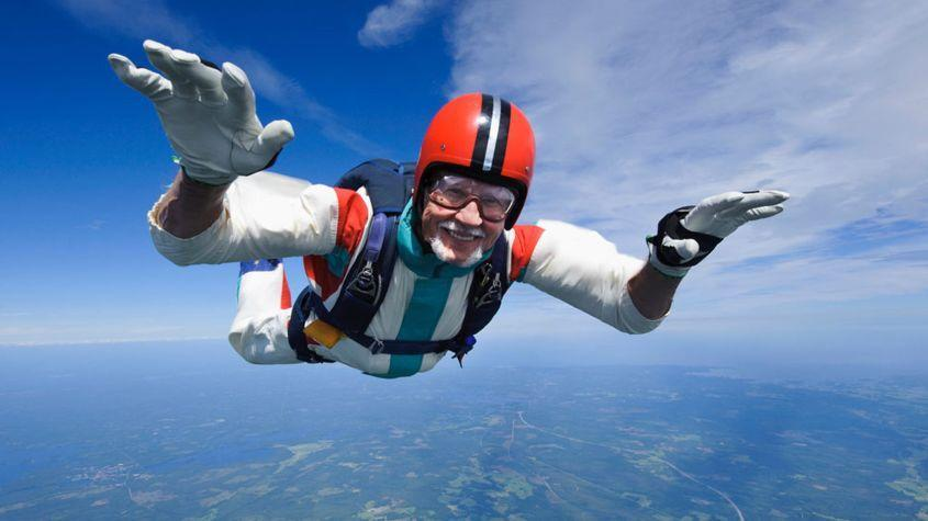 An older skydiver smiles as he freefalls.