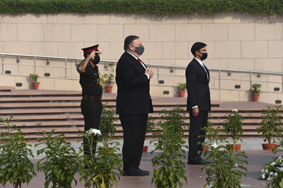 U.S. Secretary of State Mike Pompeo, center, and Secretary of Defence Mark Esper pay their tributes at the National War Memorial in New Delhi, India, Tuesday, Oct. 27, 2020. In talks on Tuesday with their Indian counterparts, Pompeo and Esper are to sign an agreement expanding military satellite information sharing and highlight strategic cooperation between Washington and New Delhi with an eye toward countering China. (Jewel Samad/Pool via AP)