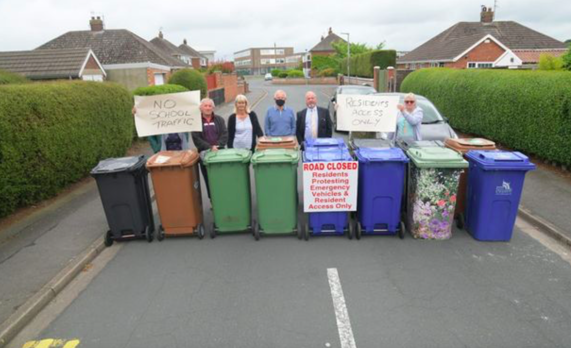 Residents set up a barricade using wheelie bins in protest at their road continuously being used by parents during school-run times. (Reach)