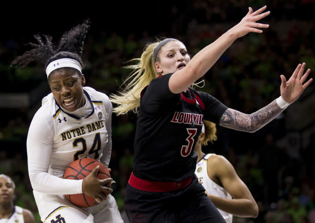 Notre Dame's Arike Ogunbowale (24) grabs a rebound next to Louisville's Sam Fuehring (3) during the first half of an NCAA college basketball game Thursday, Jan. 10, 2019, in South Bend, Ind. (AP Photo/Robert Franklin)