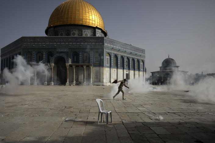 A Palestinian man runs away from tear gas during clashes with Israeli security forces in front of the Dome of the Rock Mosque at the Al Aqsa Mosque compound in Jerusalem's Old City Monday, May 10, 2021. Israeli police clashed with Palestinian protesters at a flashpoint Jerusalem holy site on Monday, the latest in a series of confrontations that is pushing the contested city to the brink of eruption. Palestinian medics said at least 180 Palestinians were hurt in the violence at the Al-Aqsa Mosque compound, including 80 who were hospitalized. (AP Photo/Mahmoud Illean)