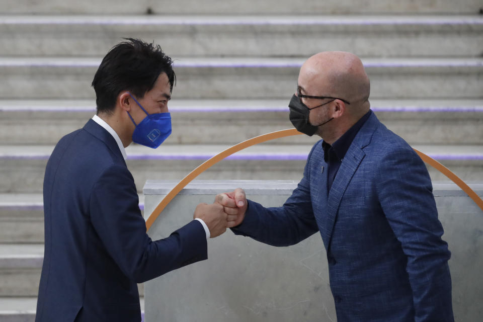 Japan's Environment Minister Shinjirō Koizumi is welcomed by Italian Minister for Ecological Transition Roberto Cingolani as he arrives at Palazzo Reale in Naples, Italy, Thursday, July 22, 2021, to take part in a G20 meeting on environment, climate and energy. (AP Photo/Salvatore Laporta)