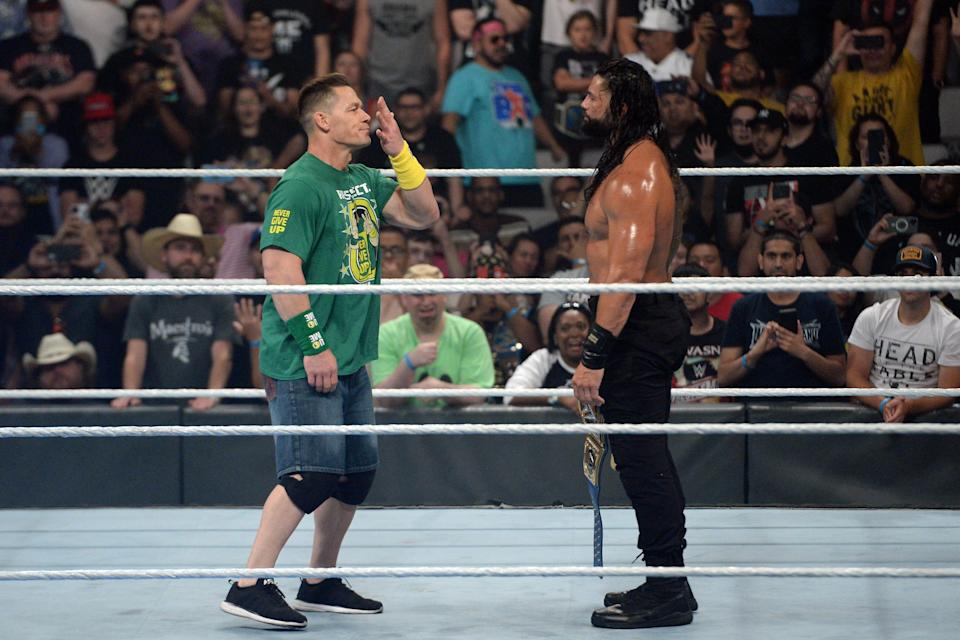 """John Cena (left) returned to WWE to confront Universal champ Roman Reigns at the """"Money in the Bank"""" event."""