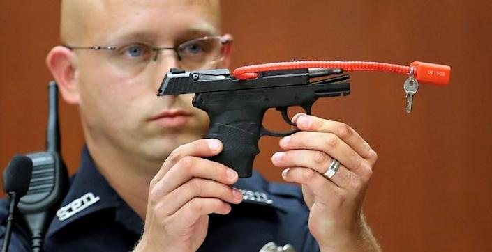 Sanford police officer Timothy Smith holds up the gun that was used to  kill Trayvon Martin, while testifying during George Zimmerman's murder trial in Seminole circuit court in Sanford, Florida, June 28, 2013. REUTERS/Joe Burbank/Pool/File Photo