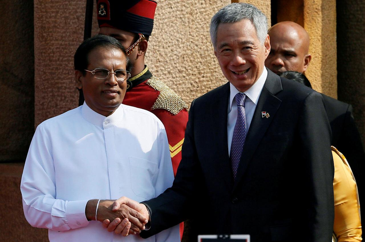 Singapore Prime Minister Lee Hsien Loong (L) shakes hands with Sri Lankan President Maithripala Sirisena in Colombo, Sri Lanka January 23, 2018. REUTERS/Dinuka Liyanawatte