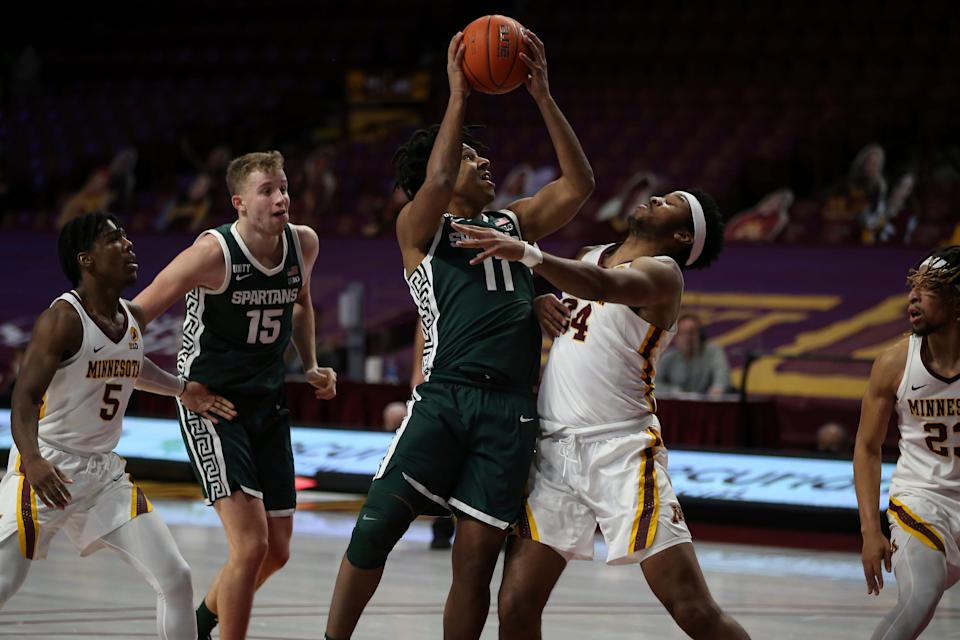 Michigan State's A.J. Hoggard (11) pushes up to the basket against Minnesota's Eric Curry (24) during the second half of an NCAA college basketball game, Monday, Dec. 28, 2020, in Minneapolis. Minnesota won 81-56.