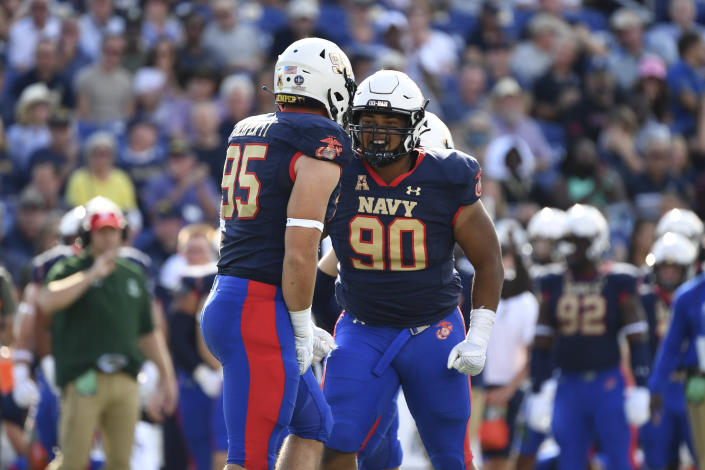 Navy defensive end Jacob Busic (95) is greeted by defensive lineman Donald Berniard Jr. (90) after a tackle during an NCAA college football game against Air Force, Saturday, Sept. 11, 2021, in Annapolis, Md. (AP Photo/Terrance Williams)