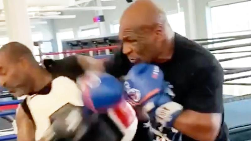 Mike Tyson (pictured right) throwing a punch at trainer Rafael Cordeiro (pictured left).