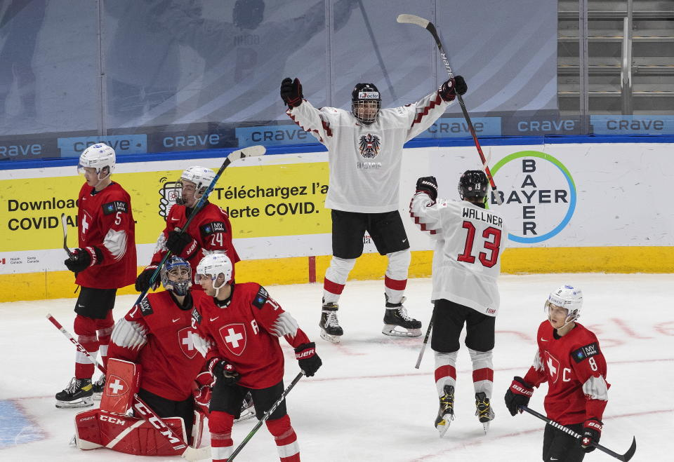 Austria's Mathias Bohm and Leon Wallner (13) celebrate a goal against Switzerland during the third period of a game in preparation for the IIHF World Junior Hockey Championships, in Edmonton, Alberta, Tuesday, Dec. 22, 2020. (Jason Franson/The Canadian Press via AP)