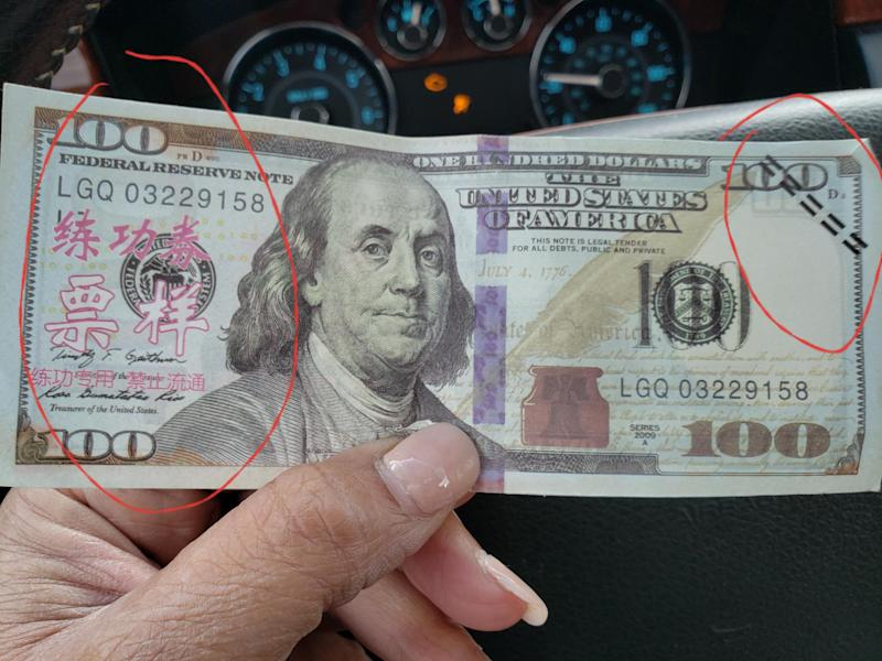 The money that Tiffany Kelly purchased from Amazon has bright red chinese characters and dark dashes across the numerals to denote the bank note is fake. (Credit: Tiffany Kelly)