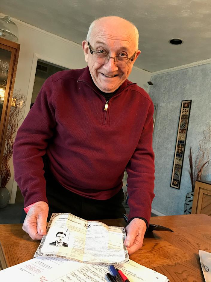 Max Glauben displays his naturalization papers at his dining room table in 2018.