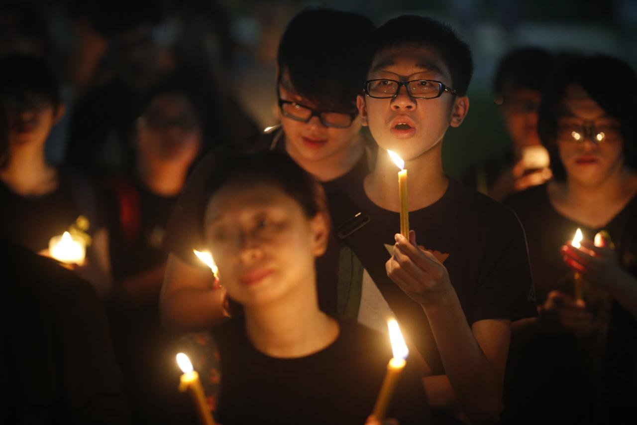 "People sing a song by Hong Kong band Beyond during a candlelight vigil in solidarity with protesters of the ""Occupy Central"" movement in Hong Kong, at Hong Lim Park Speakers' Corner in Singapore October 1, 2014. REUTERS/Edgar Su (SINGAPORE - Tags: POLITICS CIVIL UNREST)"