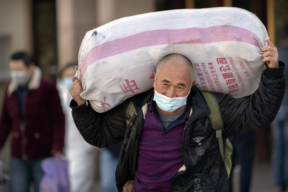 A traveler wearing a face mask to protect against the spread of the coronavirus carries his luggage as he walks out of an exit at the Beijing Railway Station in Beijing, Thursday, Jan. 28, 2021. Efforts to dissuade Chinese from traveling for Lunar New Year appeared to be working. Beijing's main train station was largely quiet on the first day of the travel rush and estimates of passenger totals were smaller than in past years. (AP Photo/Mark Schiefelbein)