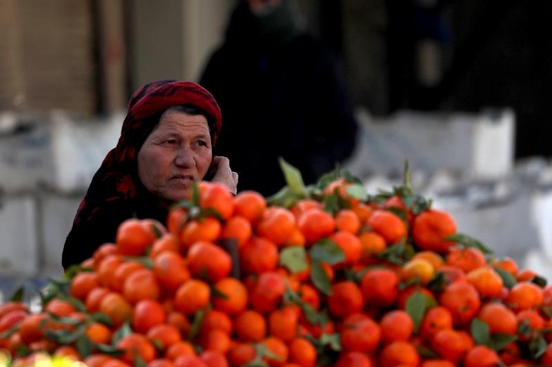 A Syrian woman sits by clementines in the northern Syrian town of Manbij, controlled by Kurdish-dominated Syrian Democratic Forces (SDF), on December 29, 2018 (AFP Photo/Delil SOULEIMAN)