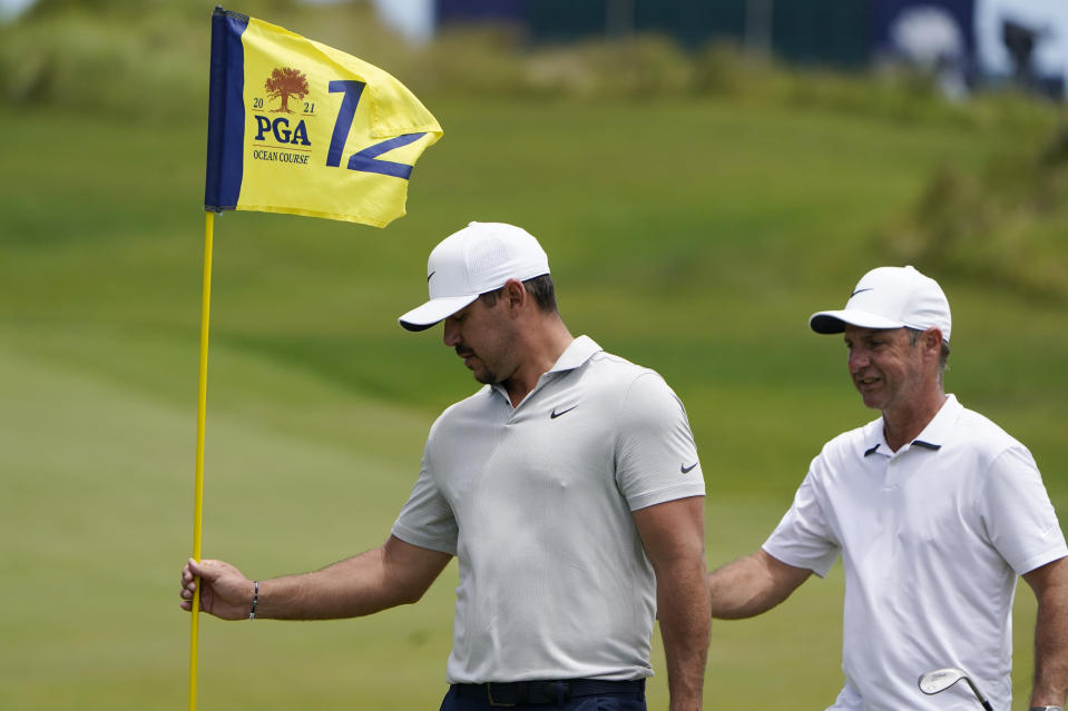 Brooks Koepka grabs the flag on the 12th hole during a practice round at the PGA Championship golf tournament on the Ocean Course Wednesday, May 19, 2021, in Kiawah Island, S.C. (AP Photo/Chris Carlson)