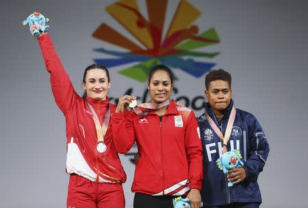 Weightlifting - Gold Coast 2018 Commonwealth Games - Women's 69kg Final - Carrara Sports Arena 1 - Gold Coast, Australia - April 8, 2018. Gold medallist Punam Yadav of India, silver medallist Sarah Davies of England and bronze medallist Apolonia Vaivai of Fiji pose with their medals and Borobi plush dolls. REUTERS/Athit Perawongmetha