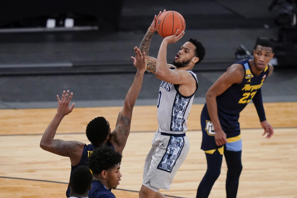 Georgetown's Jahvon Blair, center, shoots over Marquette's Symir Torrence as Jamal Cain, right, watches during the second half of an NCAA college basketball game in the Big East conference tournament Wednesday, March 10, 2021, in New York. (AP Photo/Frank Franklin II)