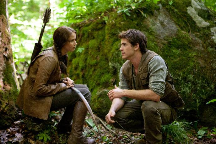 """In this image released by Lionsgate, Jennifer Lawrence portrays Katniss Everdeen, left, and Liam Hemsworth portrays Gale Hawthorne in a scene from """"The Hunger Games."""" (AP Photo/Lionsgate, Murray Close)"""