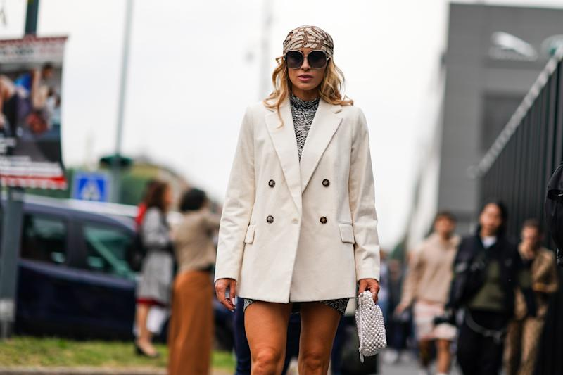 MILAN, ITALY - SEPTEMBER 22: A guest wears sunglasses, a white and brown print hair scarf, a white corduroy double-breasted jacket, a white and black hi-neck speckled mini dress, a nacreous woven beadwork bag, outside the Gucci show during Milan Fashion Week Spring/Summer 2020 on September 22, 2019 in Milan, Italy. (Photo by Edward Berthelot/Getty Images)