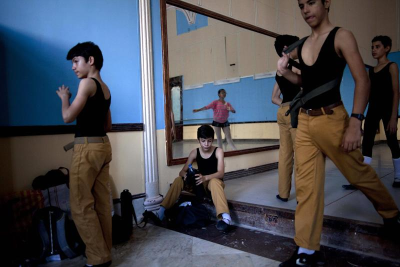 "CORRECTING MARCO TO MARCOS - In this April 3, 2013 photo, identical triplets Marcos, left, Cesar, center, and Angel Ramirez Castellanos, partially covered right, prepare for their ballet class at the National School of Ballet in Havana, Cuba. While some identical siblings find it difficult to carve out their own identities, the Ramirezes say they love it. ""For me it's a real stroke of luck being a triplet, being able to count on my brothers,"" said Cesar. ""The disadvantage is that sometimes they scold you or correct you for something that another one did."" (AP Photo/Ramon Espinosa)"