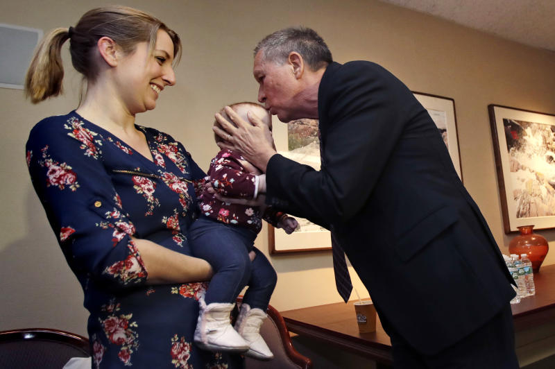Ohio Gov. John Kasich, a potential 2020 Presidential candidate, kisses the forehead of eight-month-old Cora, of Fremont, N.H. while being held by her mother Jessica in Concord, N.H., Thursday, Nov. 15, 2018. The visit marked Gov. Kasich's second trip to the state this year. (AP Photo/Charles Krupa)