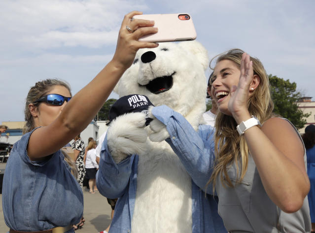Local reporters Brittany Baldassari, left, and Emmalyn Anderson take a selfie with a Polar Bear mascot during a groundbreaking ceremony for a new minor league baseball stadium, Thursday, July 11, 2019, in Worcester, Mass. Polar Park will be the new home of the Boston Red Sox' Triple-A affiliate, beginning in 2021. The club announced last year that it is moving from Pawtucket, R.I. to Worcester after failing to reach a deal for a new stadium with Rhode Island officials. (AP Photo/Elise Amendola)