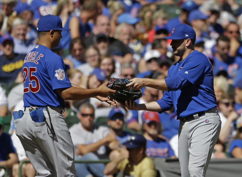 Chicago Cubs' Brian Duensing, right, exchanges gloves with Will Venable after being called in from playing the left field position to pitch during the eighth inning of a baseball game against the Milwaukee Brewers Wednesday, June 13, 2018, in Milwaukee. (AP Photo/Aaron Gash)