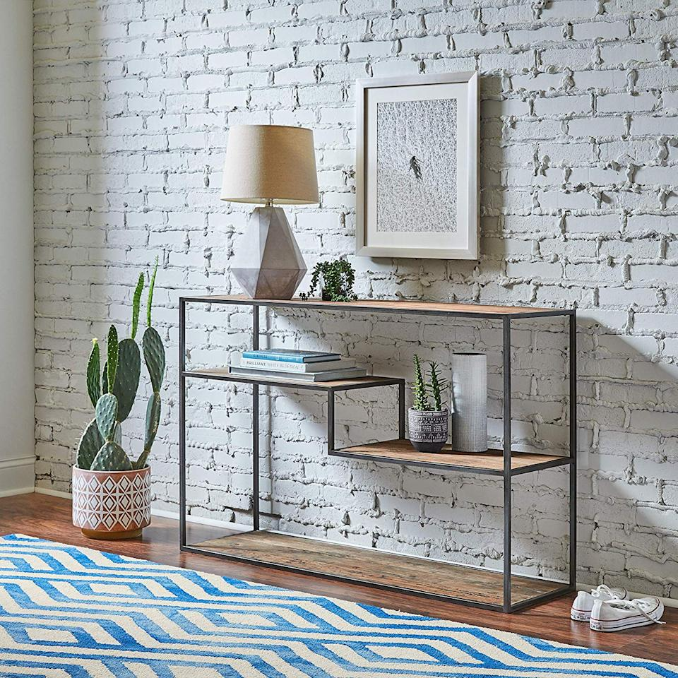 """<h3><a href=""""https://www.amazon.com/Rivet-Modern-Metal-Bookcase-Elm/dp/B07B7J8GGS/ref=sr_1_24"""" rel=""""nofollow noopener"""" target=""""_blank"""" data-ylk=""""slk:Rivet Wood & Metal Bookcase"""" class=""""link rapid-noclick-resp"""">Rivet Wood & Metal Bookcase</a> </h3><br>Opt for a thin-framed shelving unit with a simple but sharp design for storage — it will keep the space from feeling over-encumbered.<br><br><strong>Rivet</strong> Mid-Century Modern Wood & Metal Bookcase, $, available at <a href=""""https://www.amazon.com/Rivet-Modern-Metal-Bookcase-Elm/dp/B07B7J8GGS/ref=sr_1_24"""" rel=""""nofollow noopener"""" target=""""_blank"""" data-ylk=""""slk:Amazon"""" class=""""link rapid-noclick-resp"""">Amazon</a>"""