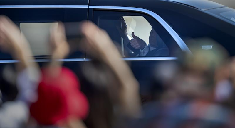 President Trump gives a thumbs-up to supporters from his limo.