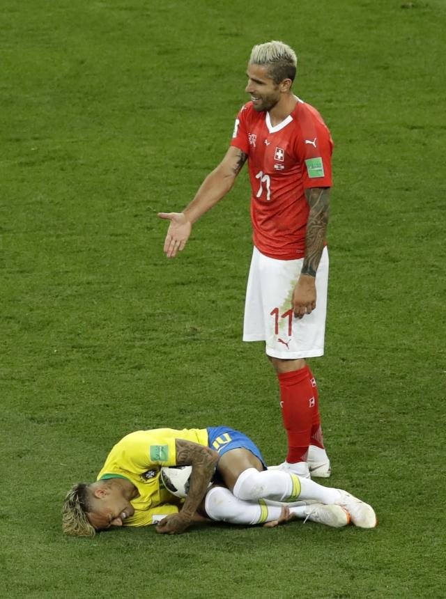 Switzerland's Valon Behrami reacts as Brazil's Neymar lies on the ground during the group E match between Brazil and Switzerland at the 2018 soccer World Cup in the Rostov Arena in Rostov-on-Don, Russia, Sunday, June 17, 2018. (AP Photo/Andrew Medichini)