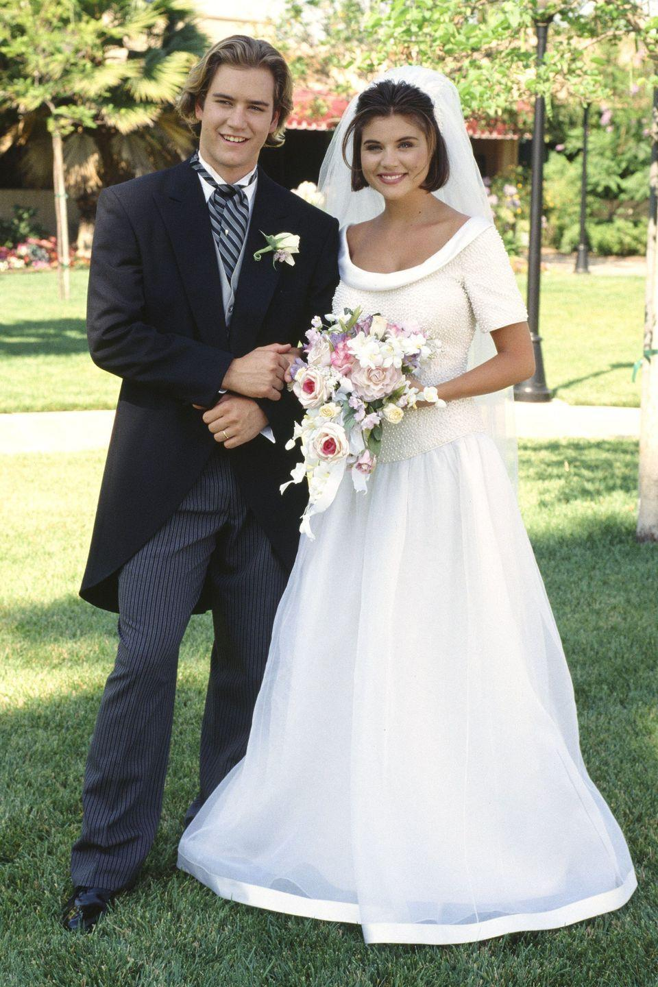 """<p>High school sweethearts Kelly and Zack married in a beautiful outdoor wedding in Las Vegas. She wore a scoop-neck wedding dress with sleeves and a veil tucked into her short hair. The nuptials took place during the series finale of <span class=""""redactor-unlink""""><em>Saved by the Bell: The College Years</em></span>. </p>"""
