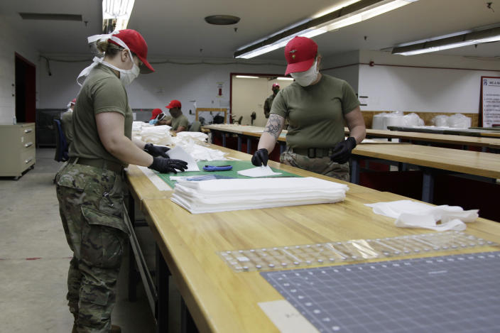 In this April 17, 2020 photo, U.S. Army soldiers work to assemble face masks in a rigger shed on Fort Bragg, N.C. N C State University donated the 4,000 meters being used to make the PPE being distributed to units across the base. (AP Photo/Sarah Blake Morgan)