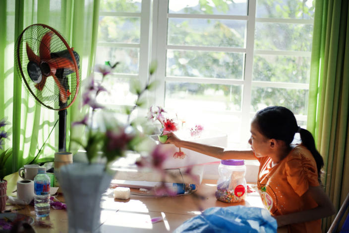 In this photo taken Aug. 7, 2012, Ho Thi Lang, 18, plugs a fake flower made by herself in a bottle at a rehabilitation center in Danang, Vietnam. The children were born with physical and mental disabilities that the center's director said were caused by their parents' exposure to the chemical dioxin in the defoliant Agent Orange. Washington was slow to respond, but on Thursday, Aug. 9, 2012 the U.S. for the first time will begin cleaning up leftover dioxin that was stored at the former military base, now part of Danang's airport. (AP Photo/Maika Elan)