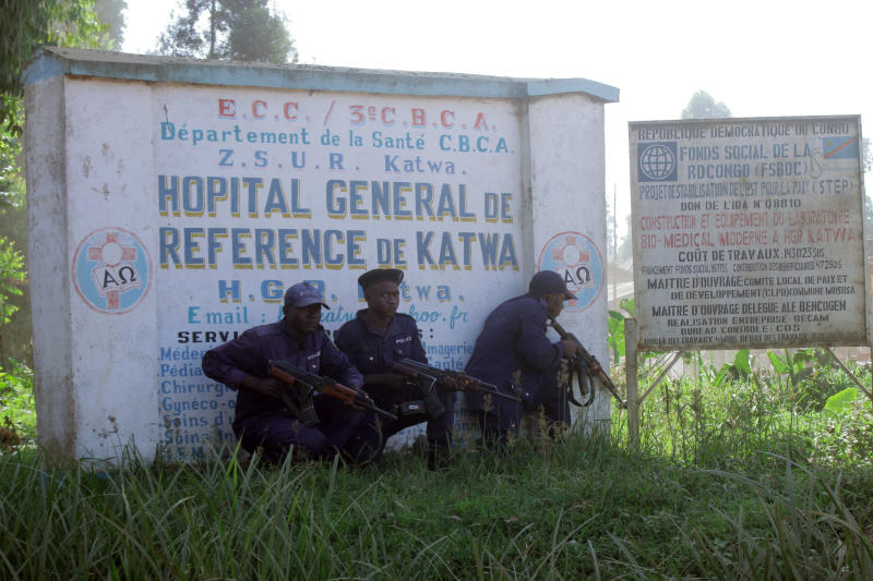 Police shelter behind a hospital sign, as they guard a hospital in Butembo, Congo, on Saturday, April 20, 2019, after militia members attacked an Ebola treatment center in the city's Katwa district overnight. Violence has deeply complicated efforts to contain what has become the second-deadliest Ebola virus outbreak in history. (AP Photo/Al-Hadji Kudra Maliro)